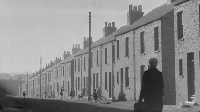 1978 MONTAGE Coal mining town with terraced houses clustered around the pits and children playing jump rope in the street / United Kingdom