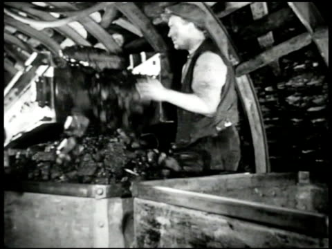 Coal moving on conveyor belt English miner shoveling MS Coal off conveyor into carts CU Coal on conveyor EXT VS Workers pushing carts w/ coal up...