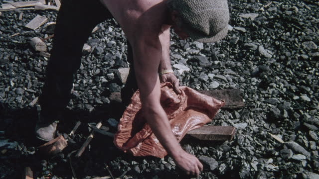 1978 montage coal picker collecting pieces of coal from the beach, couple walking on beach, pedestrians climbing staircase and sitting in front of trailer / durham, england, united kingdom - durham england stock-videos und b-roll-filmmaterial