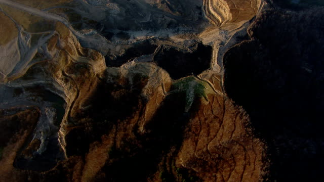 vidéos et rushes de a coal strip mine sprawls in mountainous terrain. - industrie minière