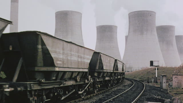 1980 ws coal train traveling on track, alongside empty track, and arriving at power station with giant smokestacks, with narrator discussing loop lines / great britain - fabriksskorsten bildbanksvideor och videomaterial från bakom kulisserna