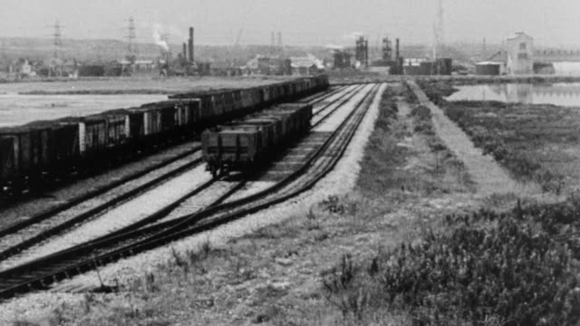 montage coal trains traveling along tracks through an industrial area, along with waiting parked wagon loads / united kingdom - british rail stock videos & royalty-free footage
