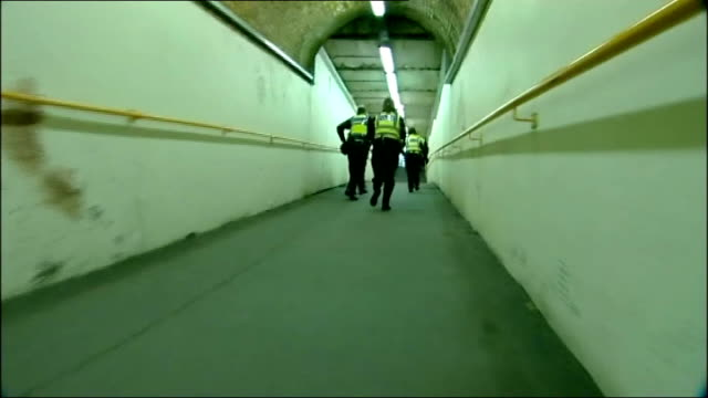 coalition government to hand out 'gangbos' to prevent gang violence lib british transport police officers running away through station tunnel track... - gang stock videos and b-roll footage