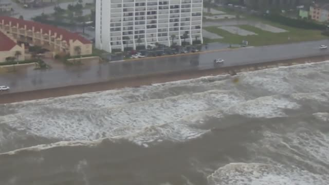 A Coast Guard Air Station Houston MH65 Dolphin helicopter crew flies over Galveston and Bolivar after Tropical Storm Bill makes landfall Tuesday June...