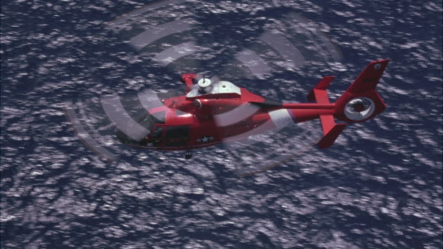 A coast guard chopper flying over the ocean.