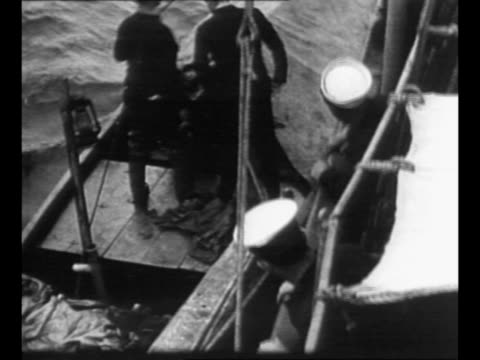 vidéos et rushes de coast guard crew on board cutter / coast guard officer gets aboard small boat at side of cutter / bottles of liquor behind glass in cabinet / small... - prohibition