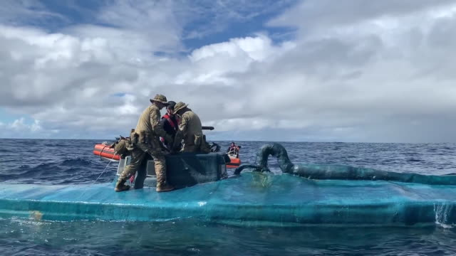 coast guard crews offload bales of seized cocaine from a semi-submersible suspected smuggling vessel onto coast guard interceptor boats for transfer... - drug trafficking stock videos & royalty-free footage