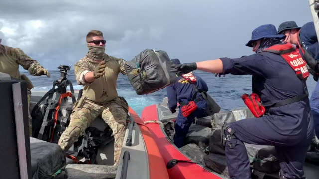 vídeos y material grabado en eventos de stock de coast guard crews offload bales of seized cocaine from a semi-submersible suspected smuggling vessel onto coast guard interceptor boats for transfer... - crime or recreational drug or prison or legal trial