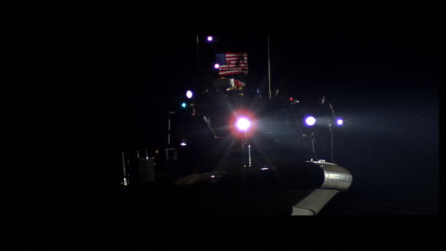 rear pov coast guard cutter steaming at night with navigation lights flashing and spotlights blazing - coast guard stock videos and b-roll footage