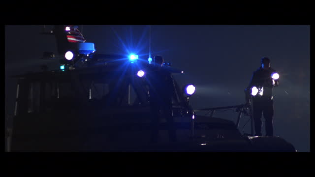 pan coast guard cutter using spotlights to search on water while searchers on shore near gazebo use flashlights - coast guard stock videos & royalty-free footage