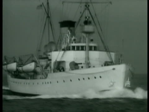 Coast Guard Cutter w/ hanging lifeboats moving on water