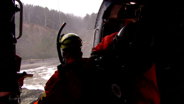a coast guard helicopter crew member kneels by an open door and prepares a hoist. - hoisting stock videos & royalty-free footage
