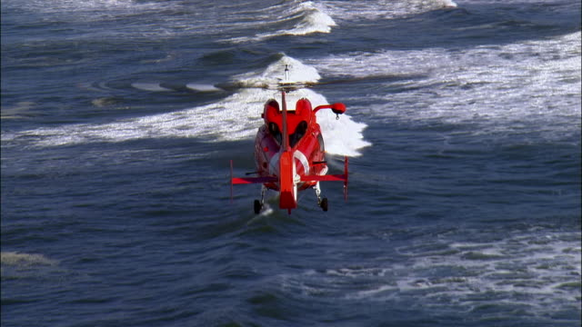 aerial coast guard helicopter flying over ocean, oregon, usa - hubschrauber stock-videos und b-roll-filmmaterial
