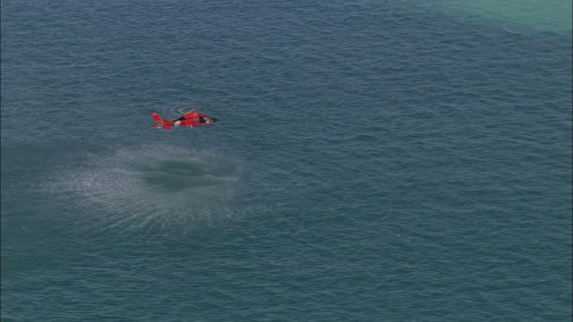 AERIAL ZO U.S. Coast Guard helicopter hovering over water during training exercise near Marathon Key, Florida, USA
