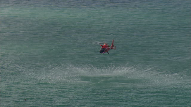 low aerial u.s. coast guard helicopter hovering over water during training exercise near marathon key, florida, usa - guardia costiera video stock e b–roll