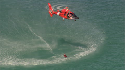 stockvideo's en b-roll-footage met low aerial u.s. coast guard helicopter hovering over water during training exercise, man saving swimmer in sea, near marathon key, florida, usa - reddingswerker