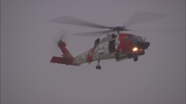 a coast guard helicopter hovers on a gloomy day. - coast guard stock videos & royalty-free footage
