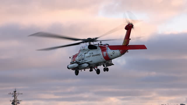 coast guard helicopter turning in air then taking off into the sky - editorial stock videos & royalty-free footage