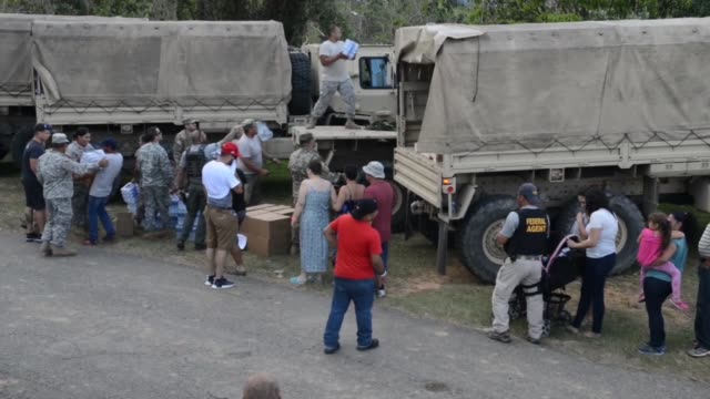 coast guard investigative service teams escort an army convoy of trucks delivering food water and tarpaulins to families living in remote mountainous... - convoy trucks stock videos and b-roll footage