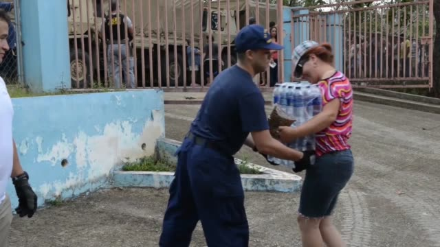 coast guard investigative service teams escort an army convoy of trucks delivering food water and tarpaulins to families living in remote mountainous... - soccorritore video stock e b–roll