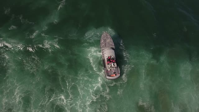 vídeos de stock e filmes b-roll de coast guard looking down over wave, rough seas, rouge wave crashing over boat water, drone aerial video, 4k, rescue, marine, pacific, tide, surge, danger, dangerous waves raw.mov - barco
