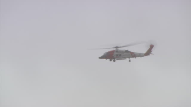 a u.s. coast guard mh-60t jayhawk helicopter flies on a rescue mission. - coast guard stock videos & royalty-free footage
