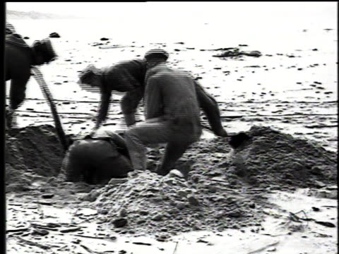 1916 ms coast guard rigging a pulley system and filling in the hole on the shore of lake michigan / united states - 掘る点の映像素材/bロール