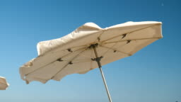 Coast of Costa del Maresme. Close-up shot of sun umbrella waving on the strong wind. Spain. 4K