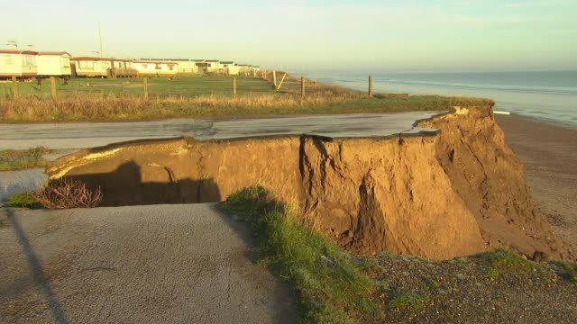 coastal erosion threatens homes in village of skipsea; england: yorkshire: skipsea: ext air views / drone footage homes on coast of skipsea and... - eroded stock videos & royalty-free footage
