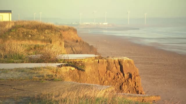 coastal erosion threatens homes in village of skipsea: general views; england: yorkshire: skipsea: ext sun rising with area of cliff eroded away in... - eroded stock videos & royalty-free footage