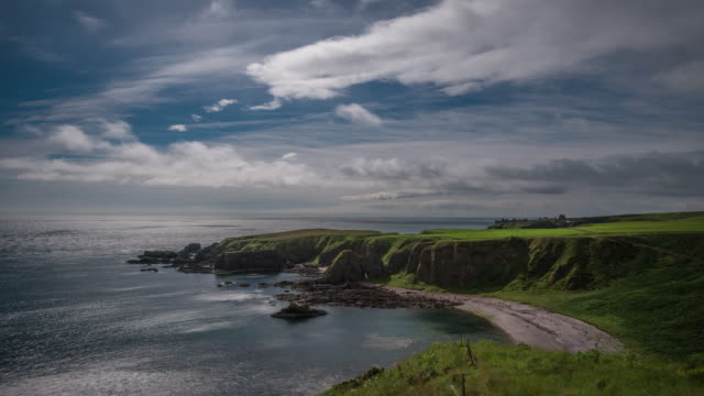 a coastal landscape looking across the shimmering waters of the north sea as low clouds passover the head land at strathlethan bay with the ruins of dunnottar castle in the distance - aberdeen schottland stock-videos und b-roll-filmmaterial