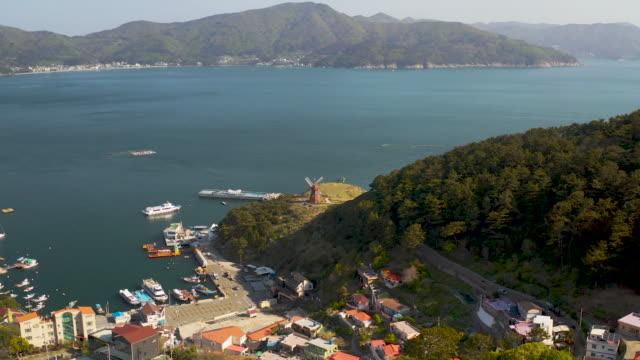 coastal road and windmill at 'windy hill' / geoje-si, gyeongsangnam-do, south korea - anker werfen stock-videos und b-roll-filmmaterial