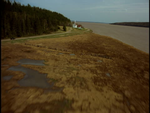 A coastal road winds along the Bay of Fundy past a small rural church.