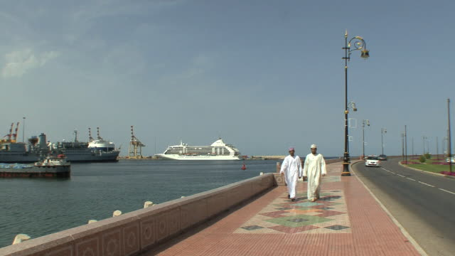 ws coastal road with two arab men passing camera, muscat, oman - 固定された点の映像素材/bロール