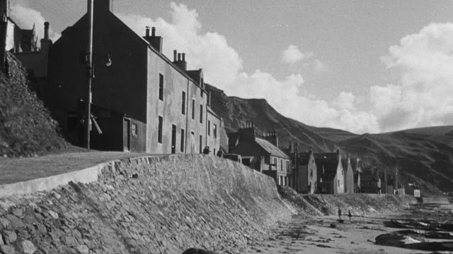 1950 montage coastal village sitting high on a bank with children running down the lane, and fisherman and wife working on fishing nets as their daughters jump rope and play jacks / united kingdom - orphan stock videos & royalty-free footage