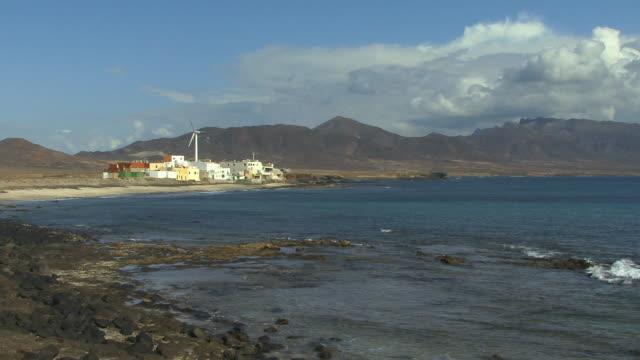 vídeos de stock, filmes e b-roll de ws coastal village with wind turbine/ puerto de la cruz, fuerteventura, canary islands - ilhas do oceano atlântico