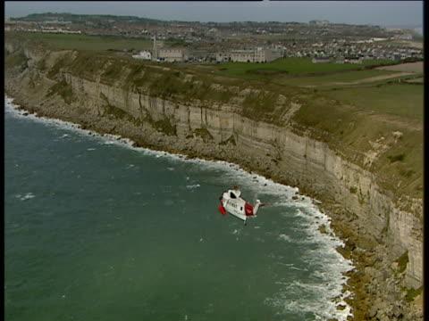 Coastguard helicopter flies over sea towards cliffs Isle of Portland