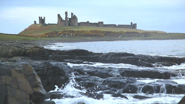 coastline and ruin of dunstanburgh castle - northumberland coast stock videos & royalty-free footage