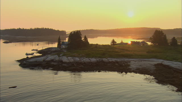 vidéos et rushes de low aerial, coastline at sunrise, andrews island, maine, usa - maine