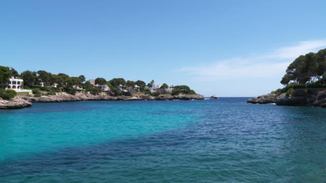 coastline near cala gran, cala d´or with tourboat. cala d´or, cala gran, majorca, balearic islands, spain, mediterranean sea. - tourboat stock videos & royalty-free footage