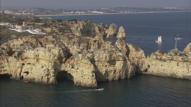 AERIAL WS ZO Coastline with sea stacks and motorboat moving by / Lagos, Faro, Portugal