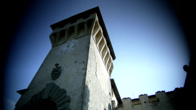 A coat of arms and a clock adorn a castle's tower in Italy. Available in HD.