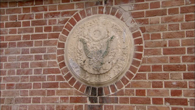 cu zi us coat of arms on brick wall of united states embassy, tehran, iran - us embassy stock videos & royalty-free footage