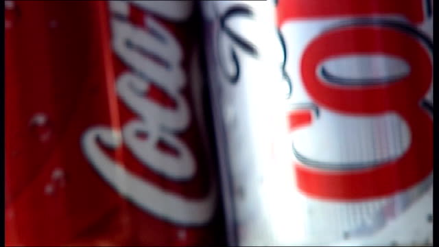 Coca Cola plans for green tea with claims it can burn calories Open fridge stacked with different brands of soft drinks Close up of Cocacola cans...