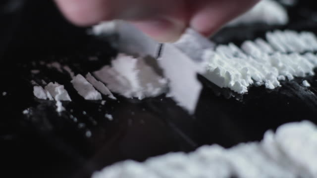 SLO MO CU Cocaine being cut into lines