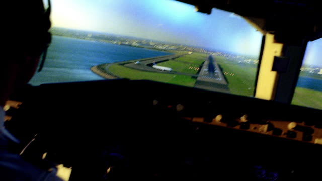 Cockpit point of view behind pilots landing airplane and approaching runway
