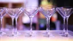 cocktail glasses on a table in a nightclub. Side view. Bar is getting ready to open