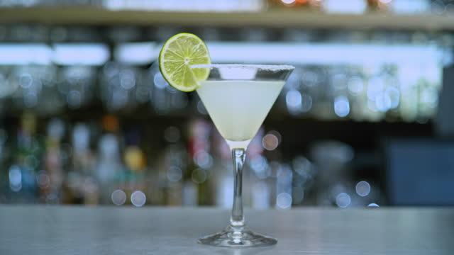 vidéos et rushes de cocktail slo mo ds dans un verre en forme de v avec une tranche de lime - verre à pied