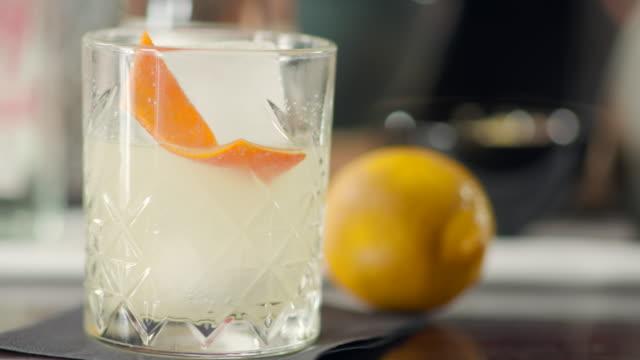 cocktail auf dem eis im trinkglas auf der bartheke - sprudelgetränk stock-videos und b-roll-filmmaterial