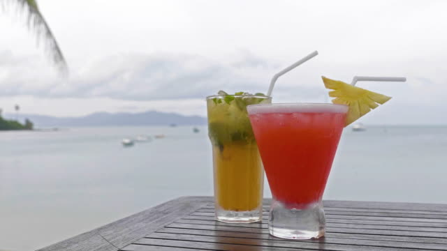 vídeos y material grabado en eventos de stock de vidrio de cócteles en la tabla con playa y vistas al mar - cóctel tropical